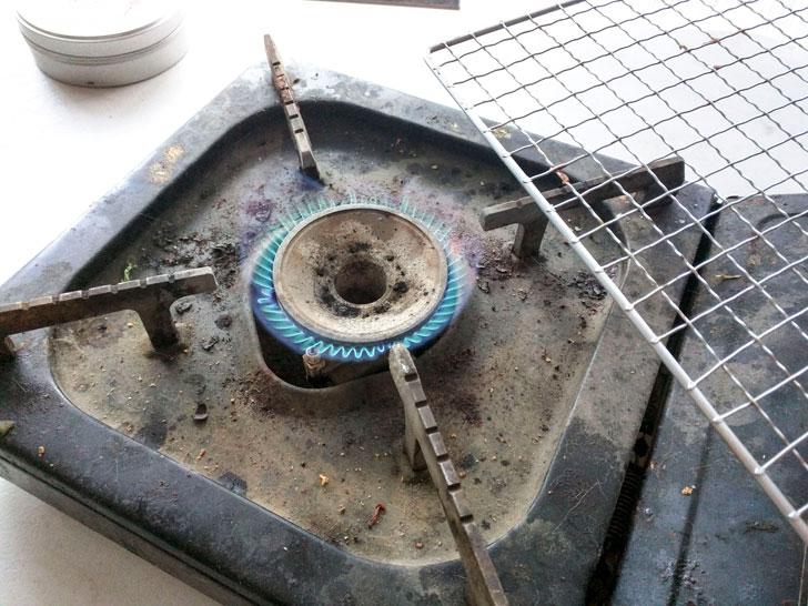 コンロの火で網を炙って殺菌